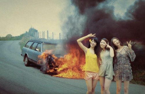 three-girls-making-peace-sign-with-car-on-fire